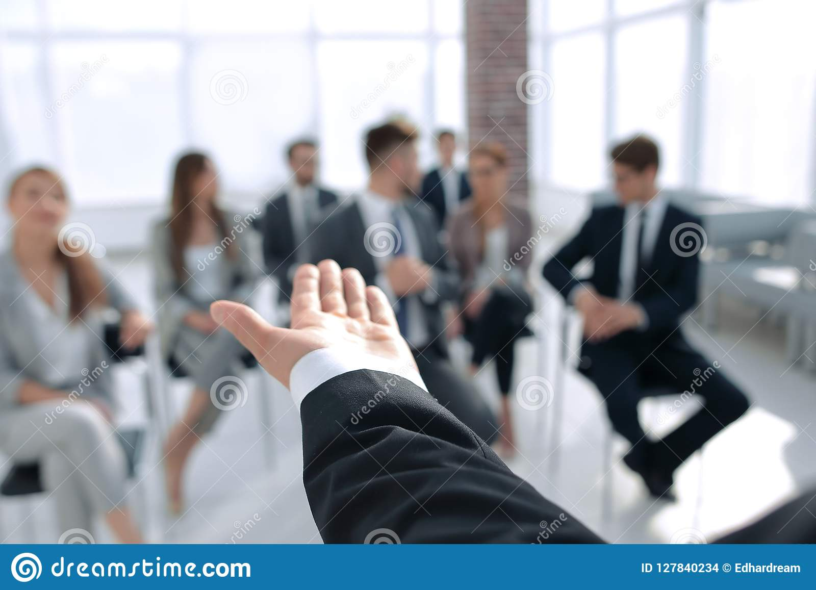 Rear view.Business coach gesturing his hand in front of a group of people.