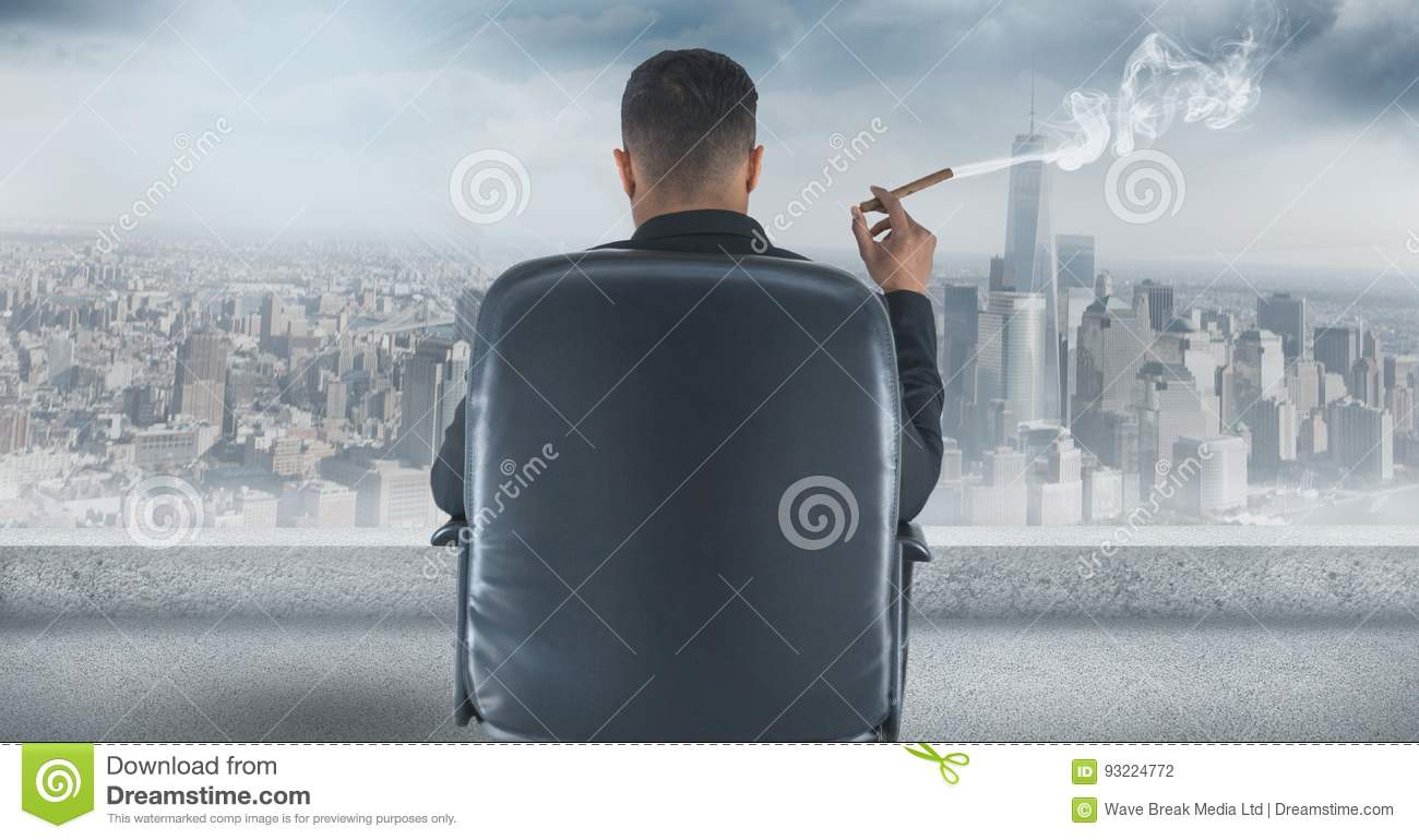 Rear view of businessman sitting on chair and looking at city while smoking cigar