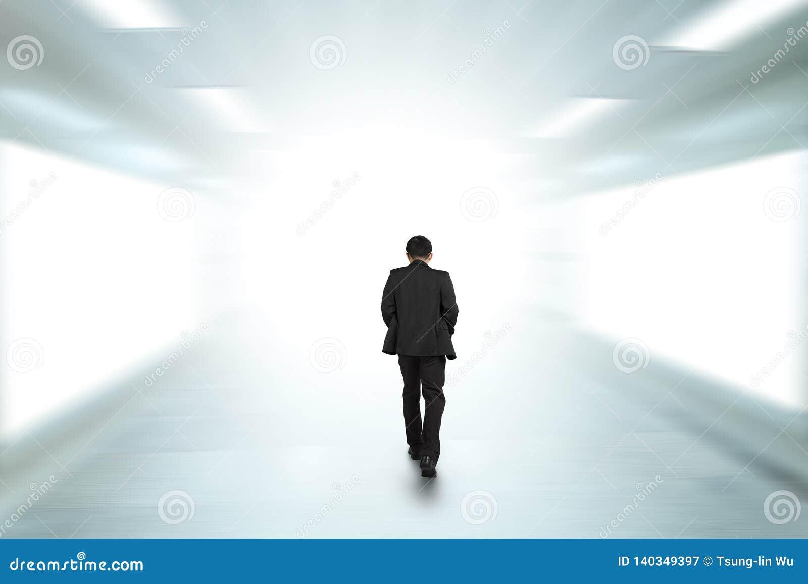 Rear view businessman walking through underpass toward bright side