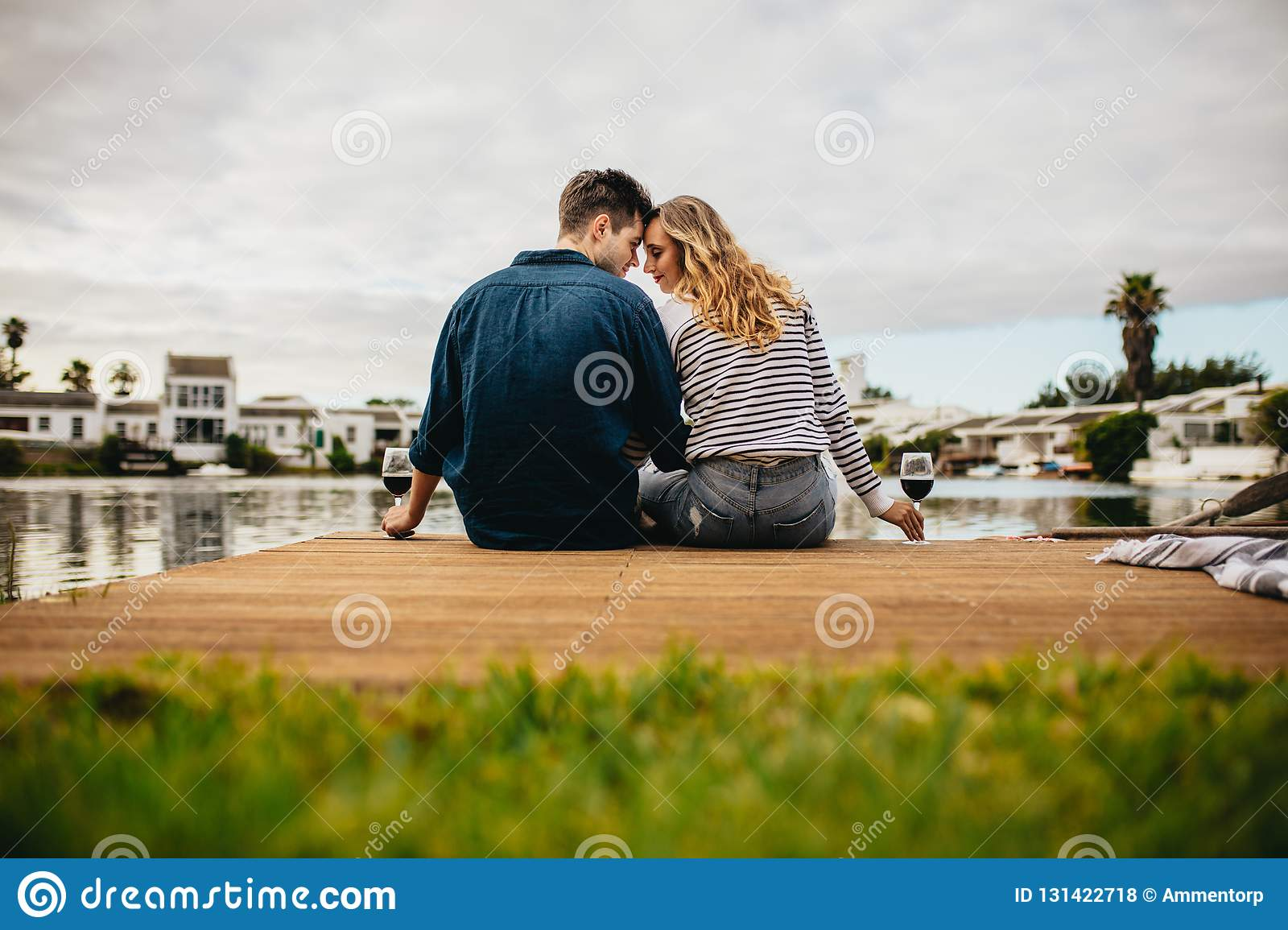 Rear view of a couple in love sitting together touching their heads near a lake. Couple on a day out sitting together holding wine
