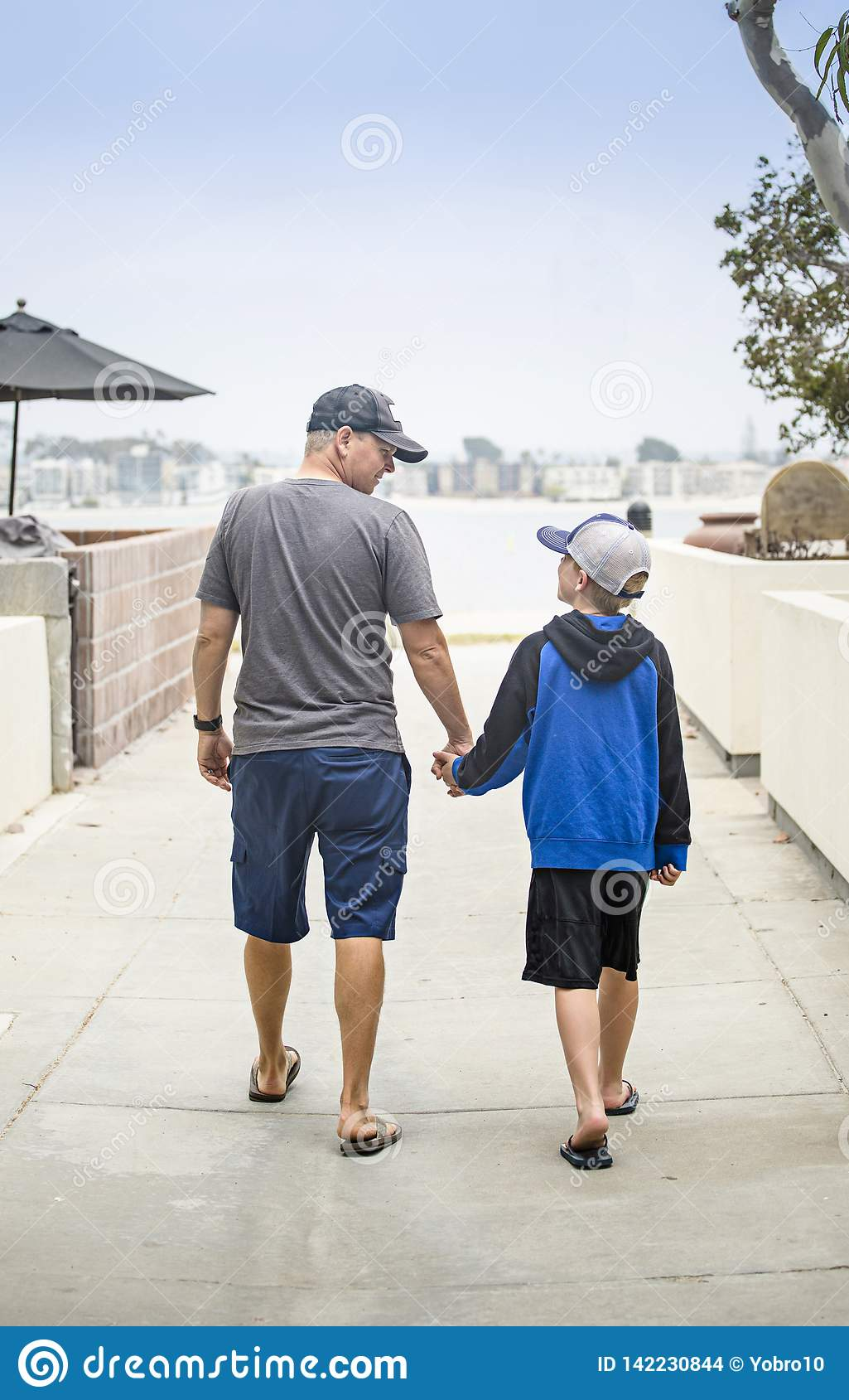 Father and Son walking hand in hand together on the sidewalk
