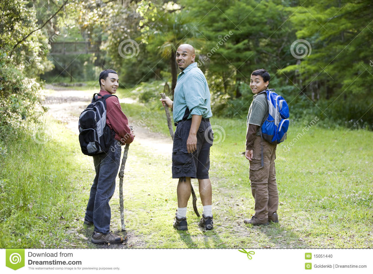 Rear View Father And Sons Hiking In Woods On Trail Stock
