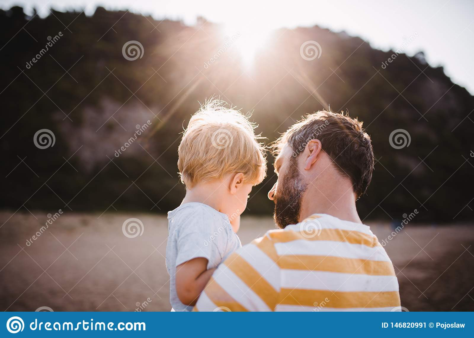 Rear view of father with a toddler boy standing on beach on summer holiday at sunset.