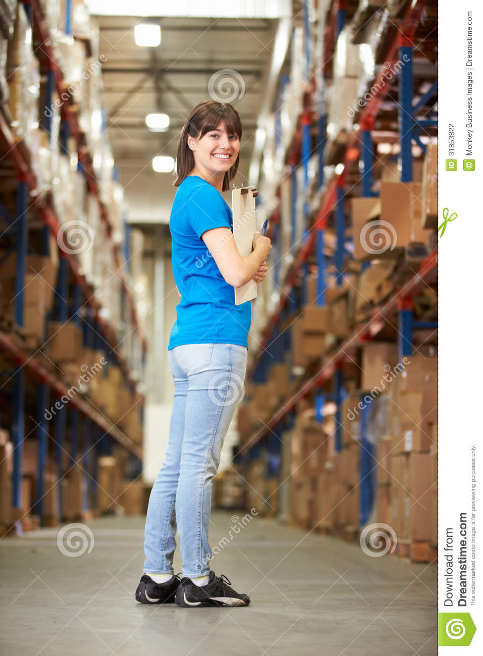rear view of female worker in distribution warehouse stock