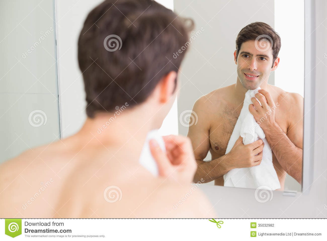 rear view of man looking at self in bathroom mirror stock photo