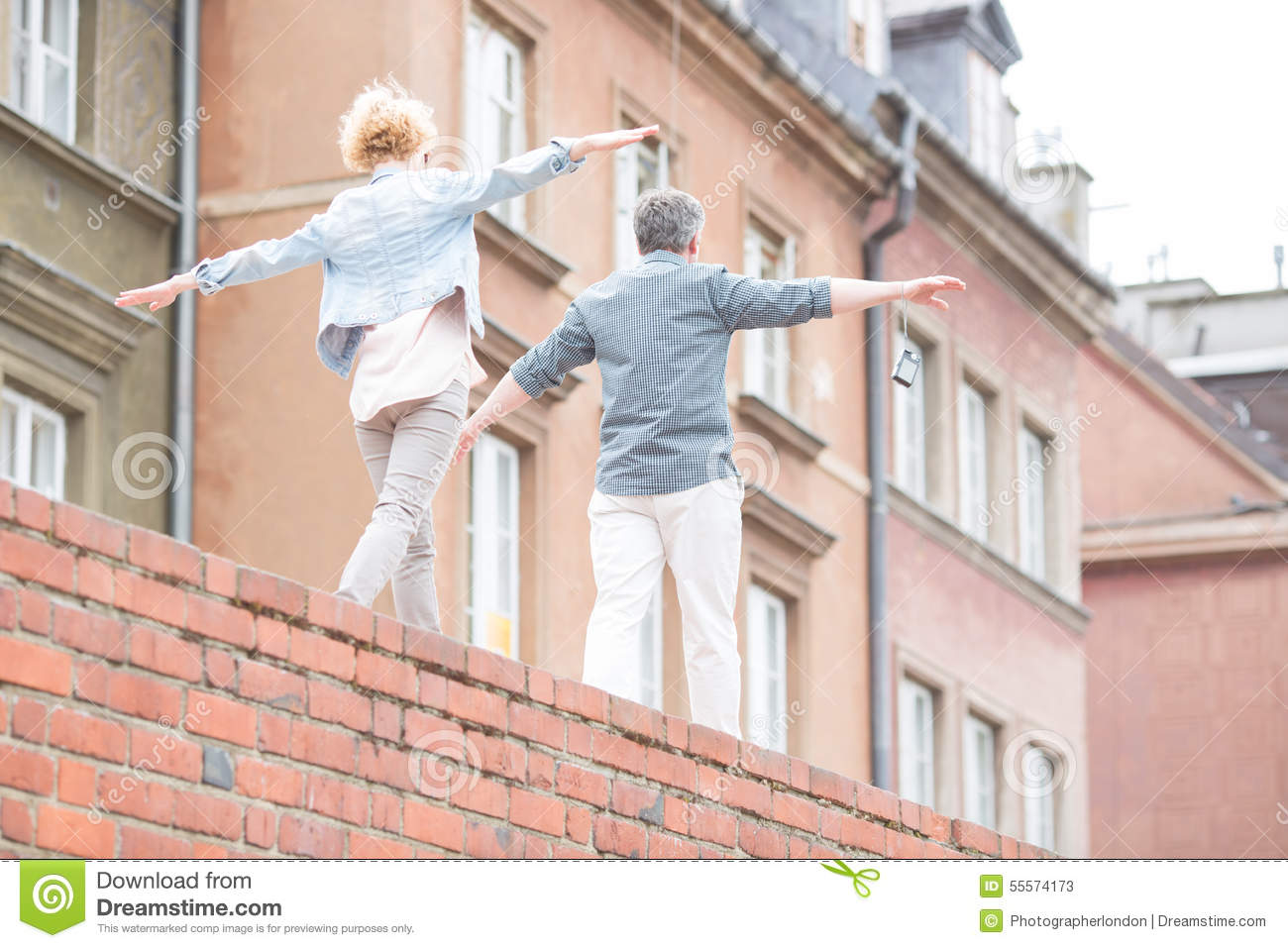Rear view of middle-aged couple with arms outstretched walking on brick wall