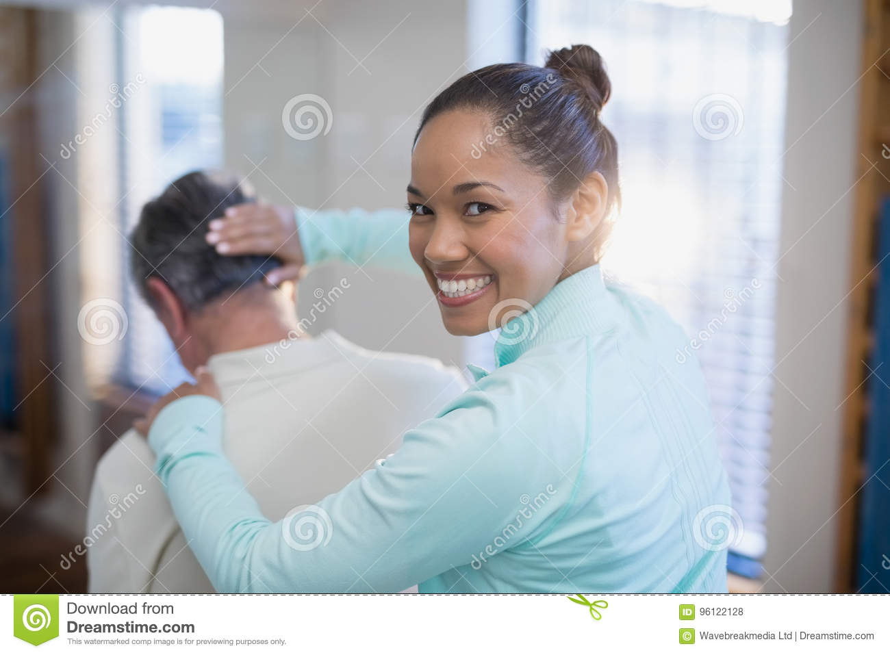 Rear view of portrait of smiling female therapist giving neck massaging to senior male patient