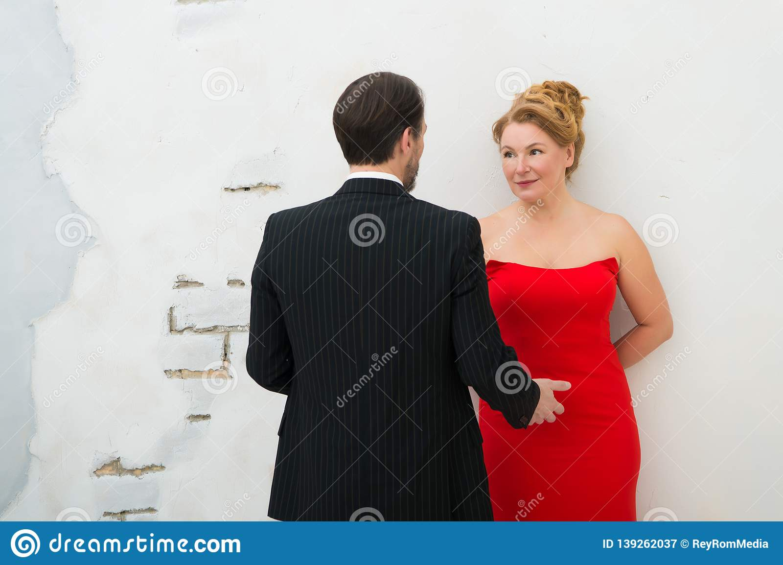 Rear view of stylish man in striped suit talking to his charming wife