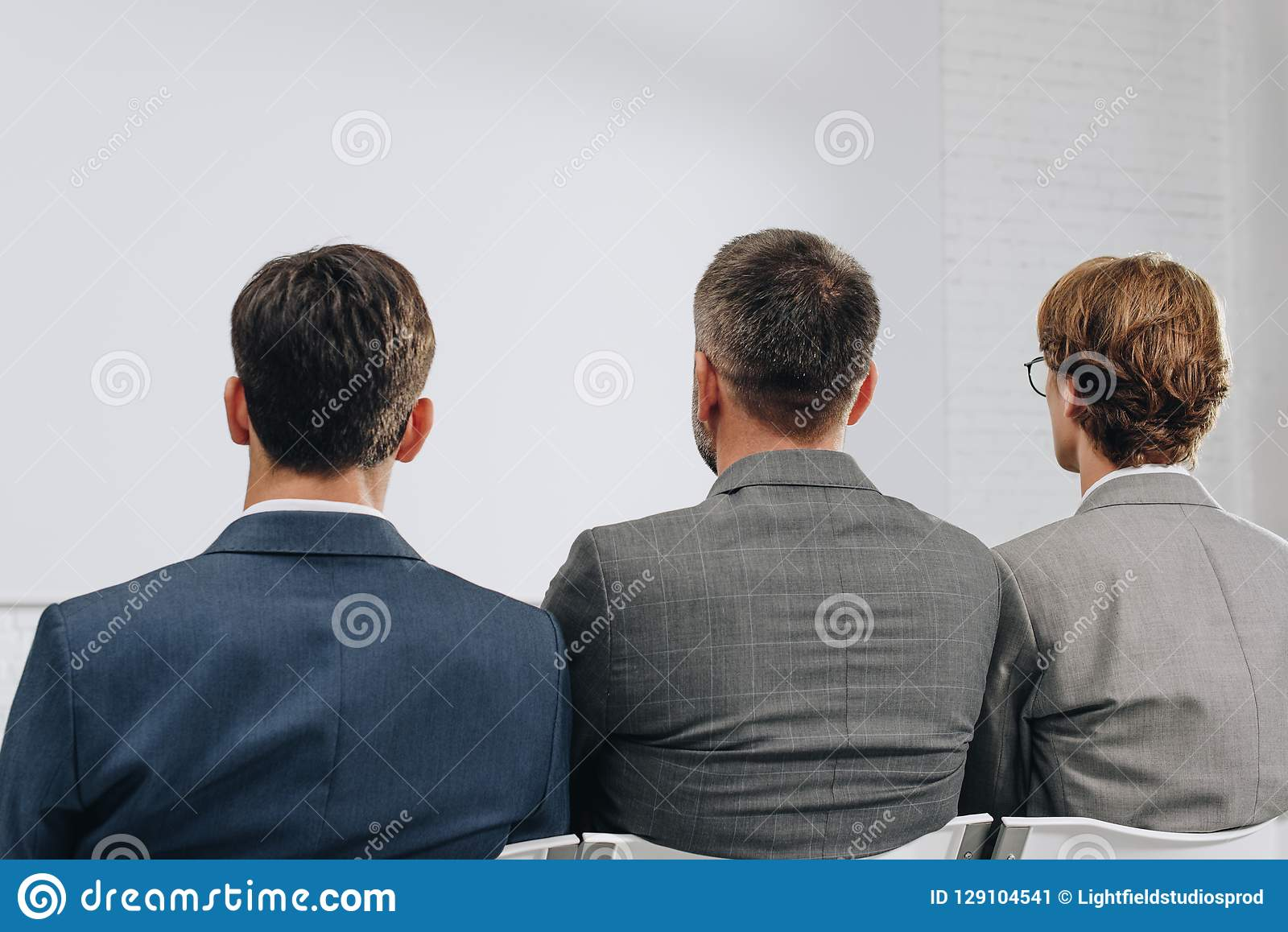 rear view of three businessmen sitting on chairs during training