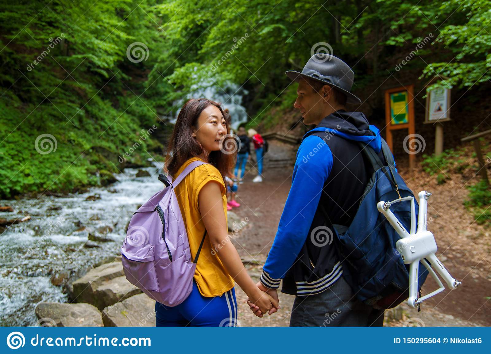 A young couple crossing a mountain stream while out walking together. Travelers stand near waterfalls.