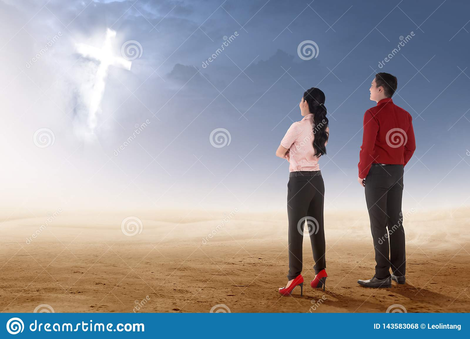 Rear view of two asian business people standing on desert and looking at glowing christian cross