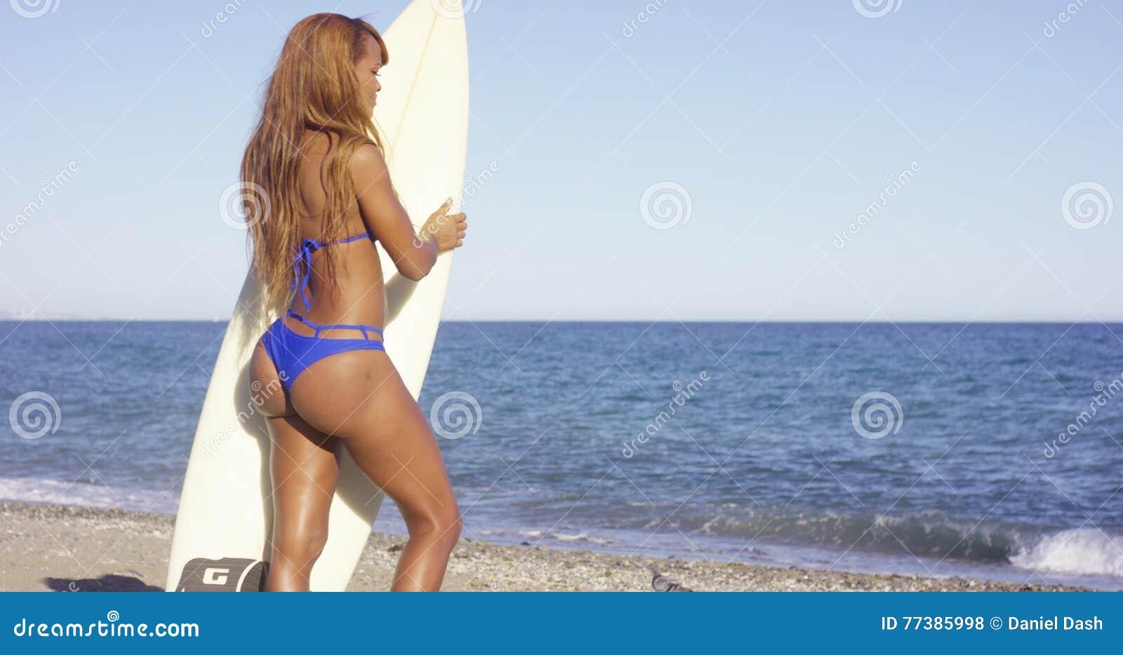 Rear View Of Woman In Bikini Holding Surfing Board Stock