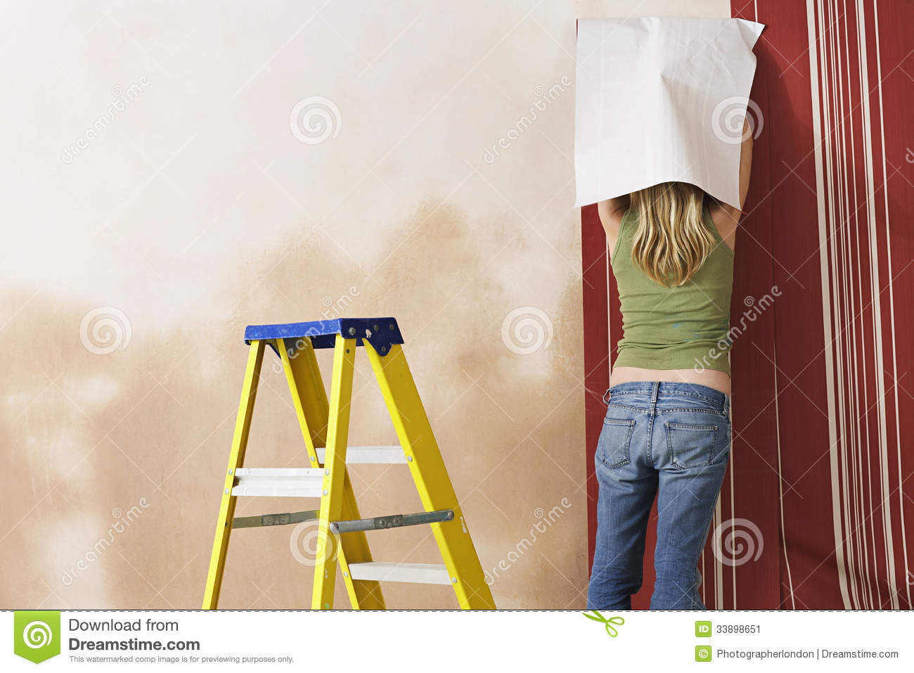 rear view of woman hanging wallpaper stock image image