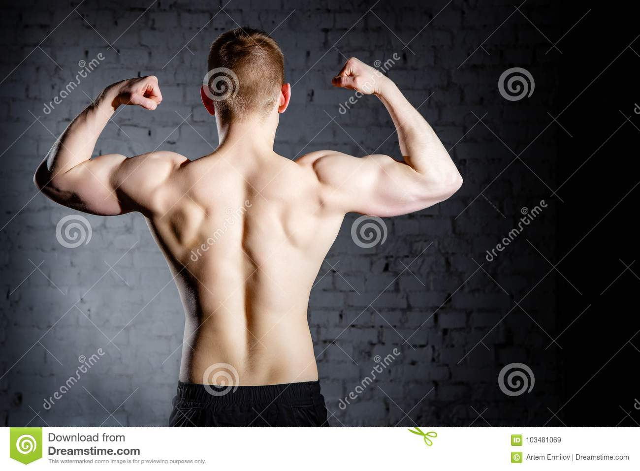 Rear view of young attractive caucasian muscular bodybuilder man with perfect body working out in sports center
