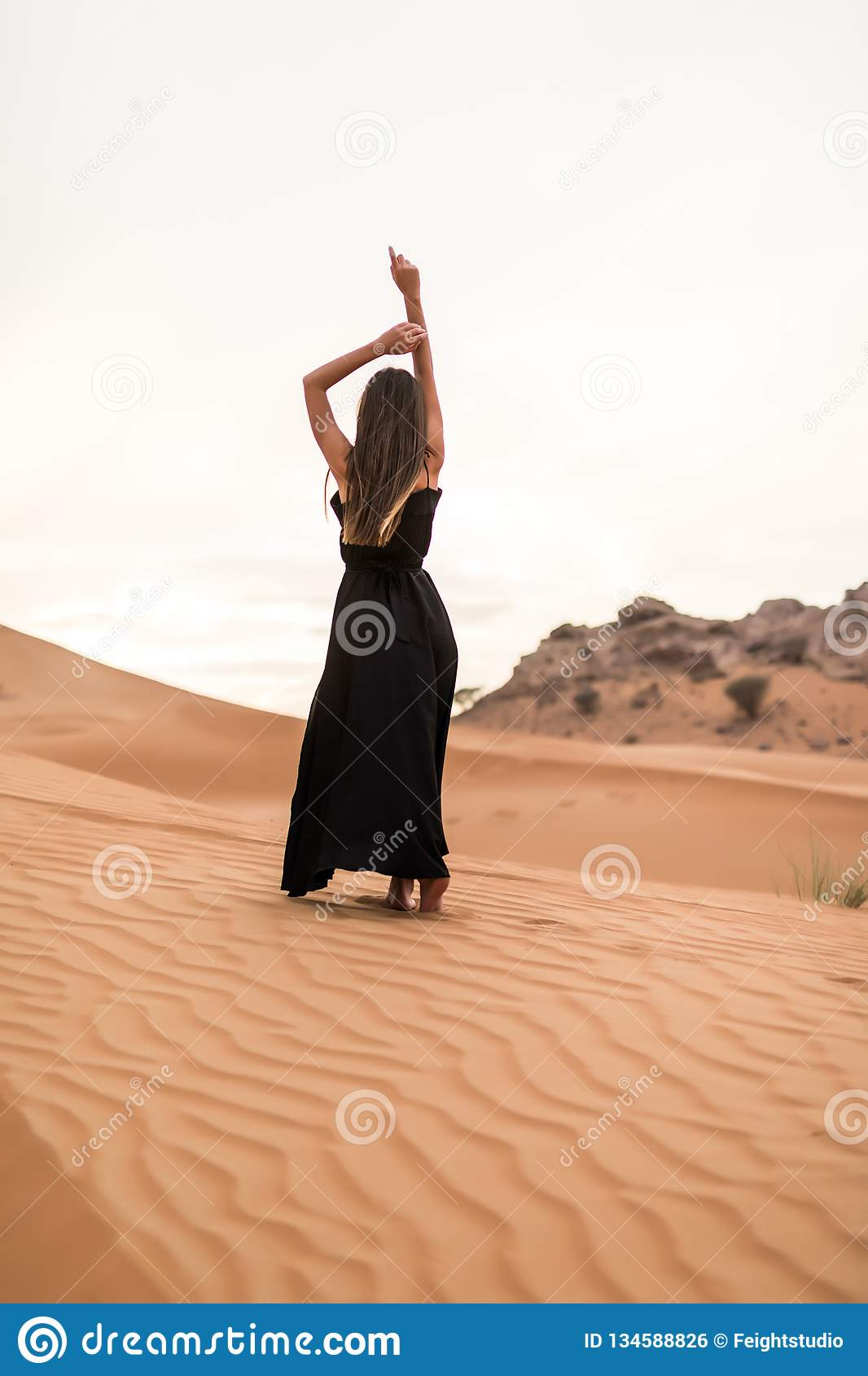 Rear view of young woman in black dress dancing in sandy desert at sunset