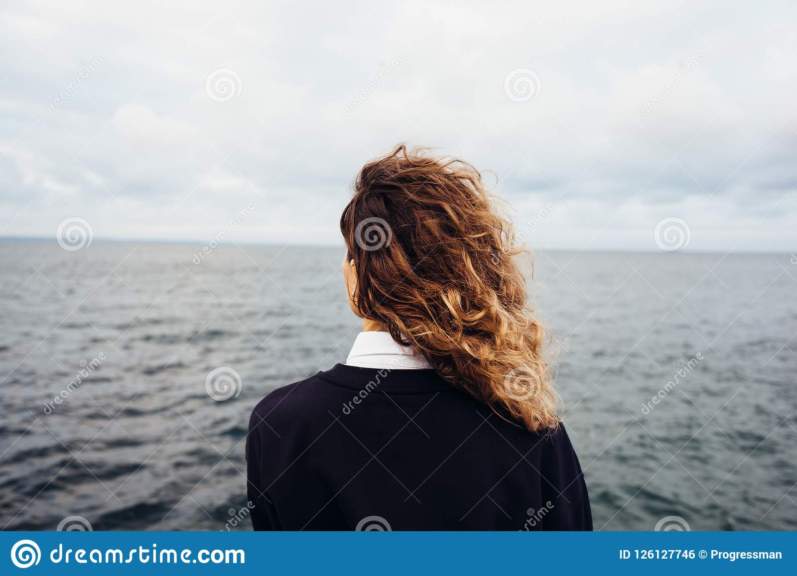 Rear view of young woman looking at overcast sky and gray sea