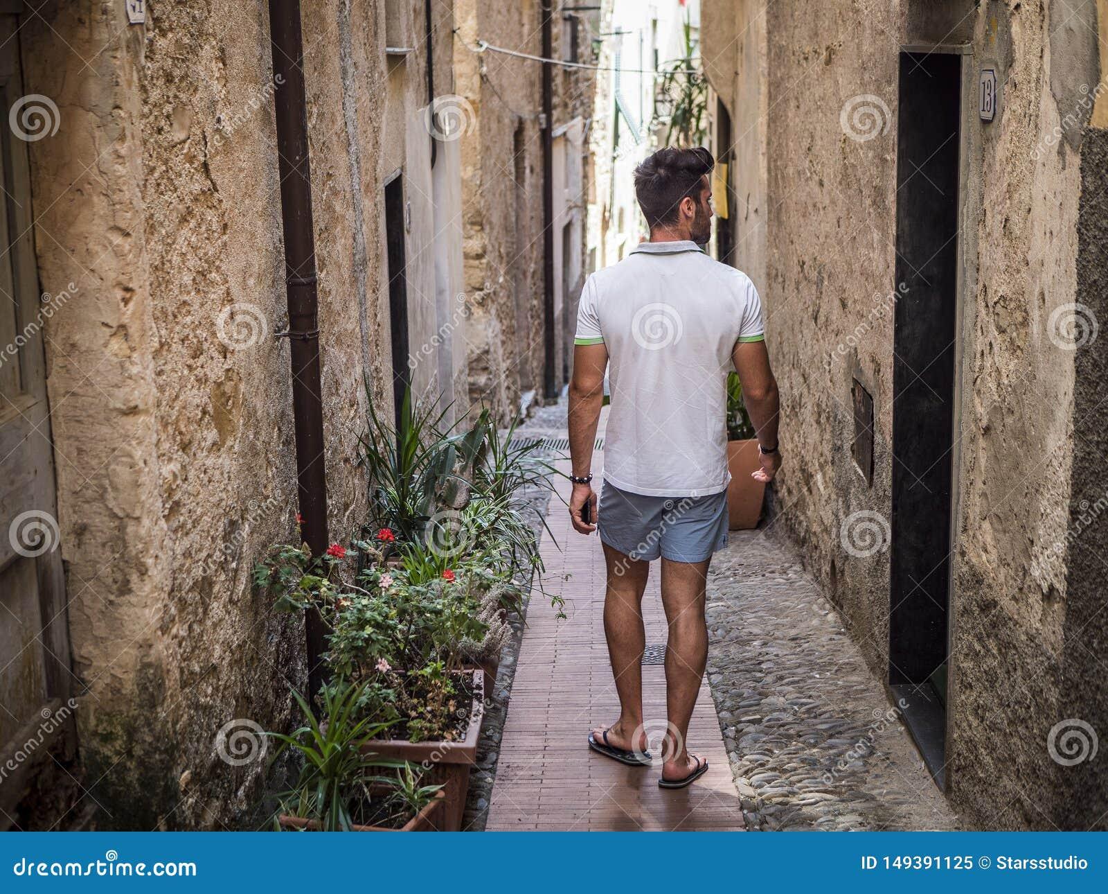 Rearview del hombre que camina en ciudad italiana vieja
