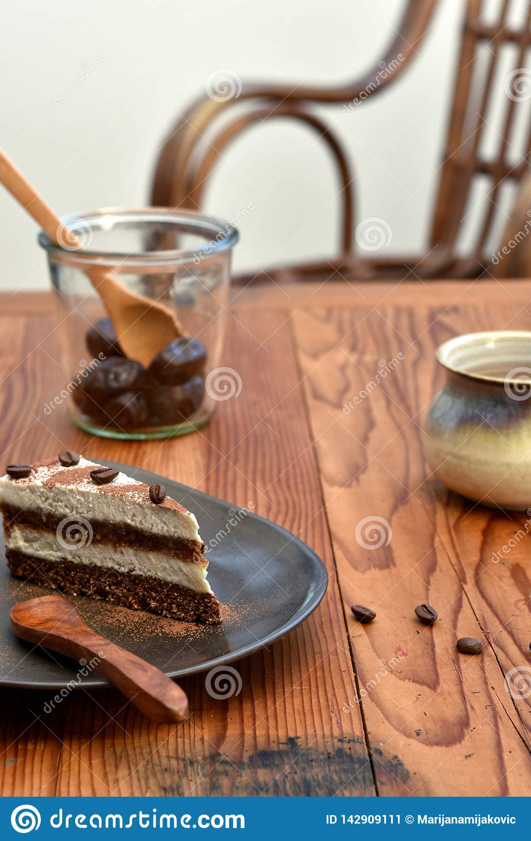 Rebanada de torta cruda del tiramisu en una placa marrón