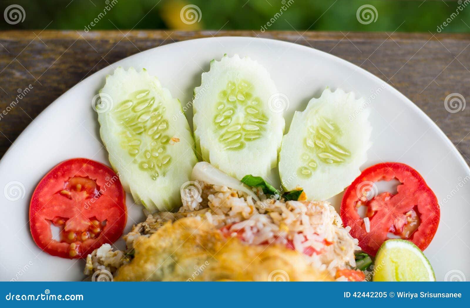 Rebanada del pepino y del tomate en el arroz frito