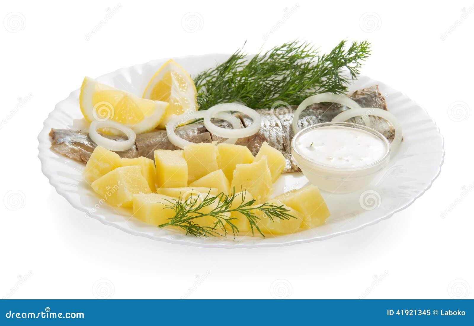Rebanadas de arenques y de una patata, anillos de cebollas