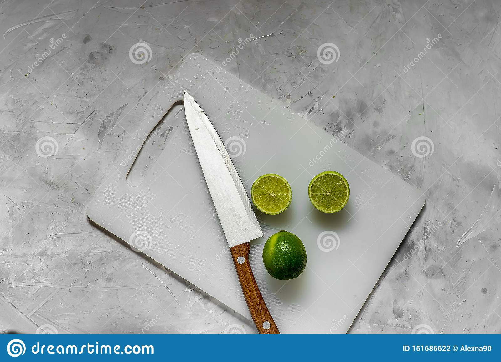 Rebanadas de cal verde fresca en el tablero de la luz de la cocina