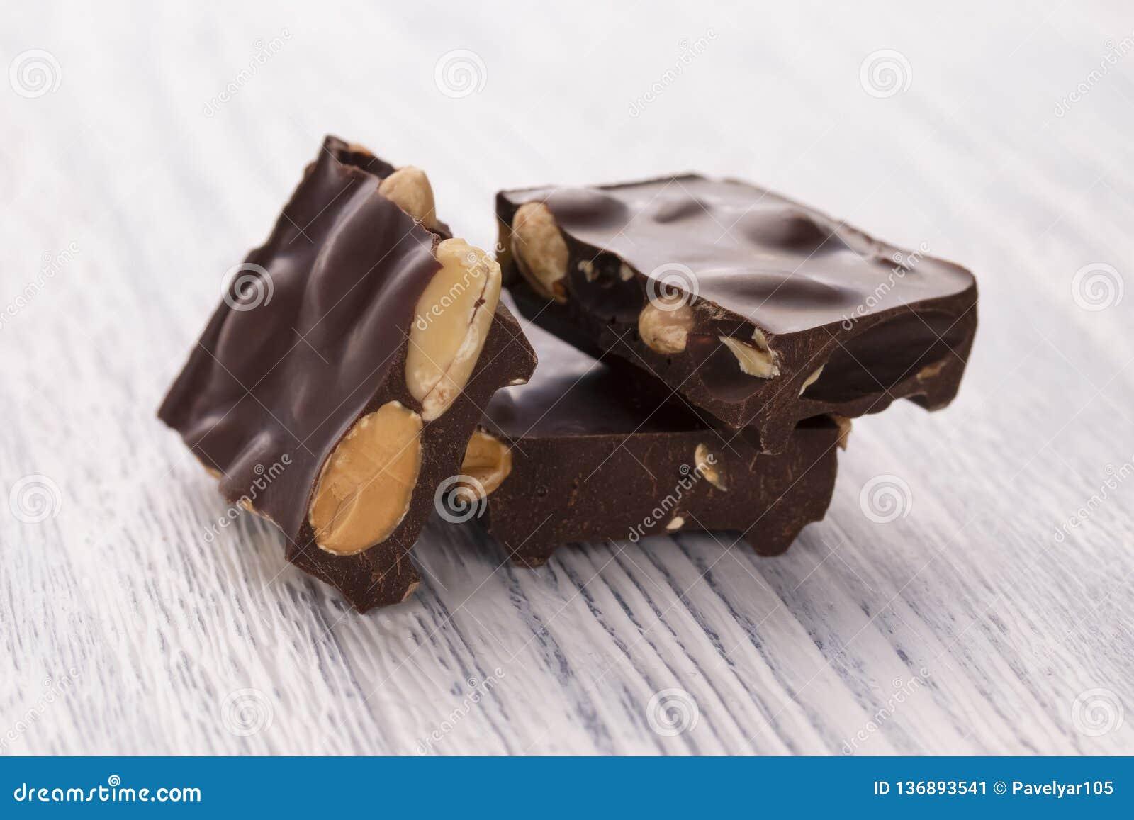 Rebanadas de chocolate oscuro con las nueces en una tabla de madera blanca