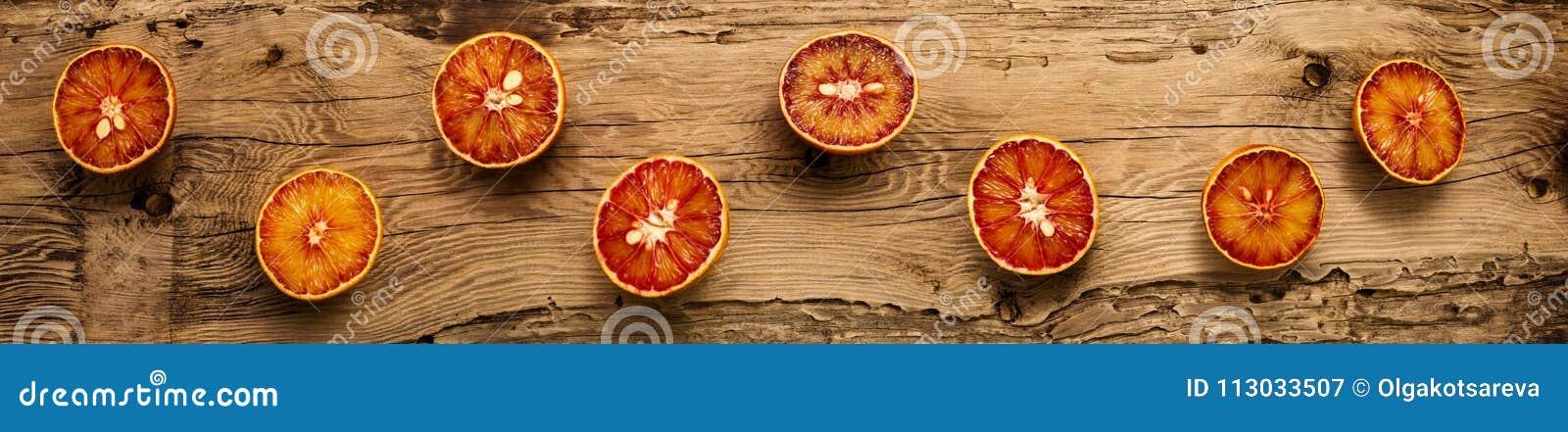 Rebanadas de la naranja de sangre en un fondo de madera del vintage, formato panorámico, visión superior