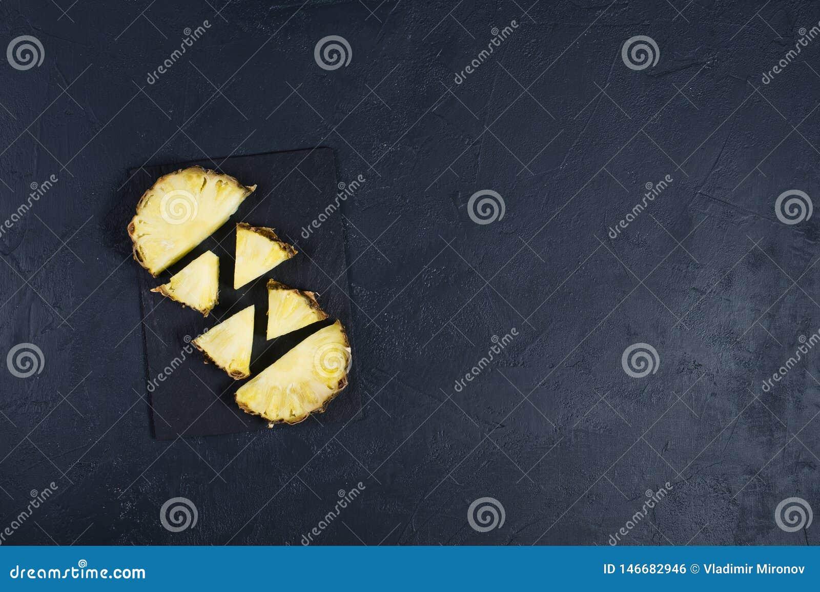 Rebanadas de la pi?a en tablero de piedra negro con el espacio para el texto