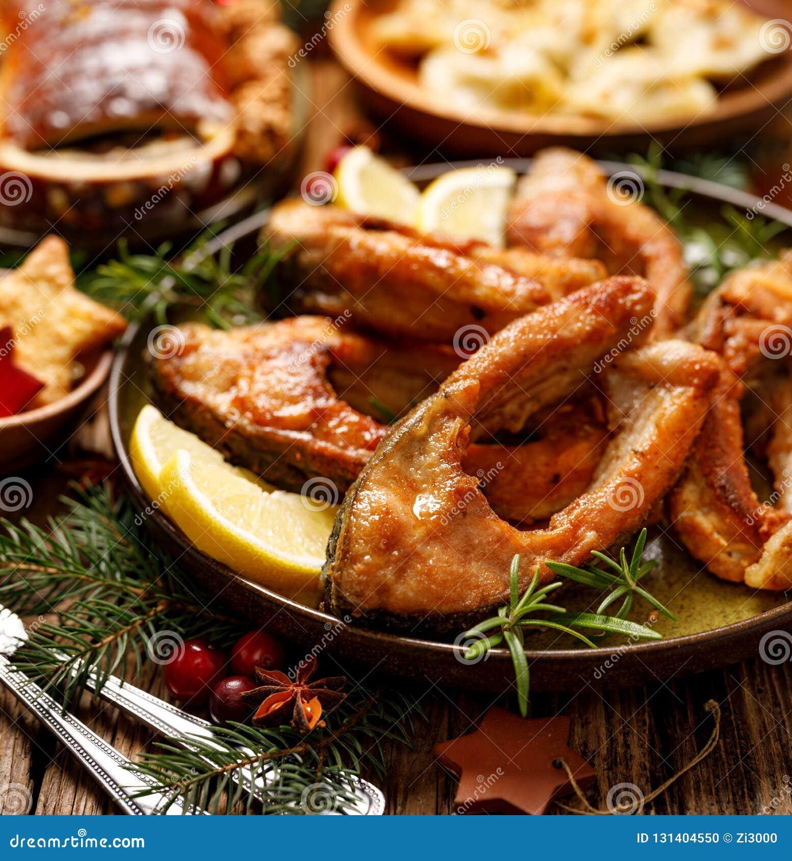 Rebanadas de pescados fritas de la carpa en una placa de cerámica, cierre para arriba Plato tradicional de la Nochebuena