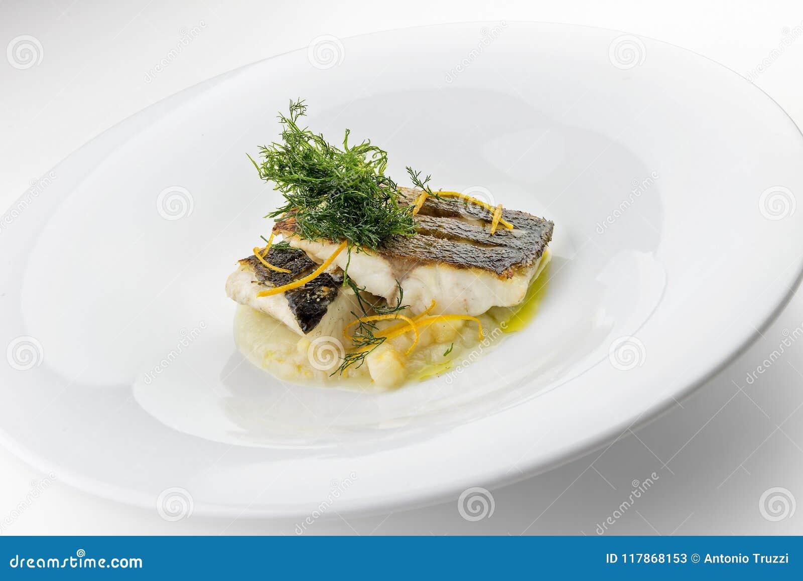 Rebanadas del plato de pescados de prendederos de la lubina en verduras trituradas