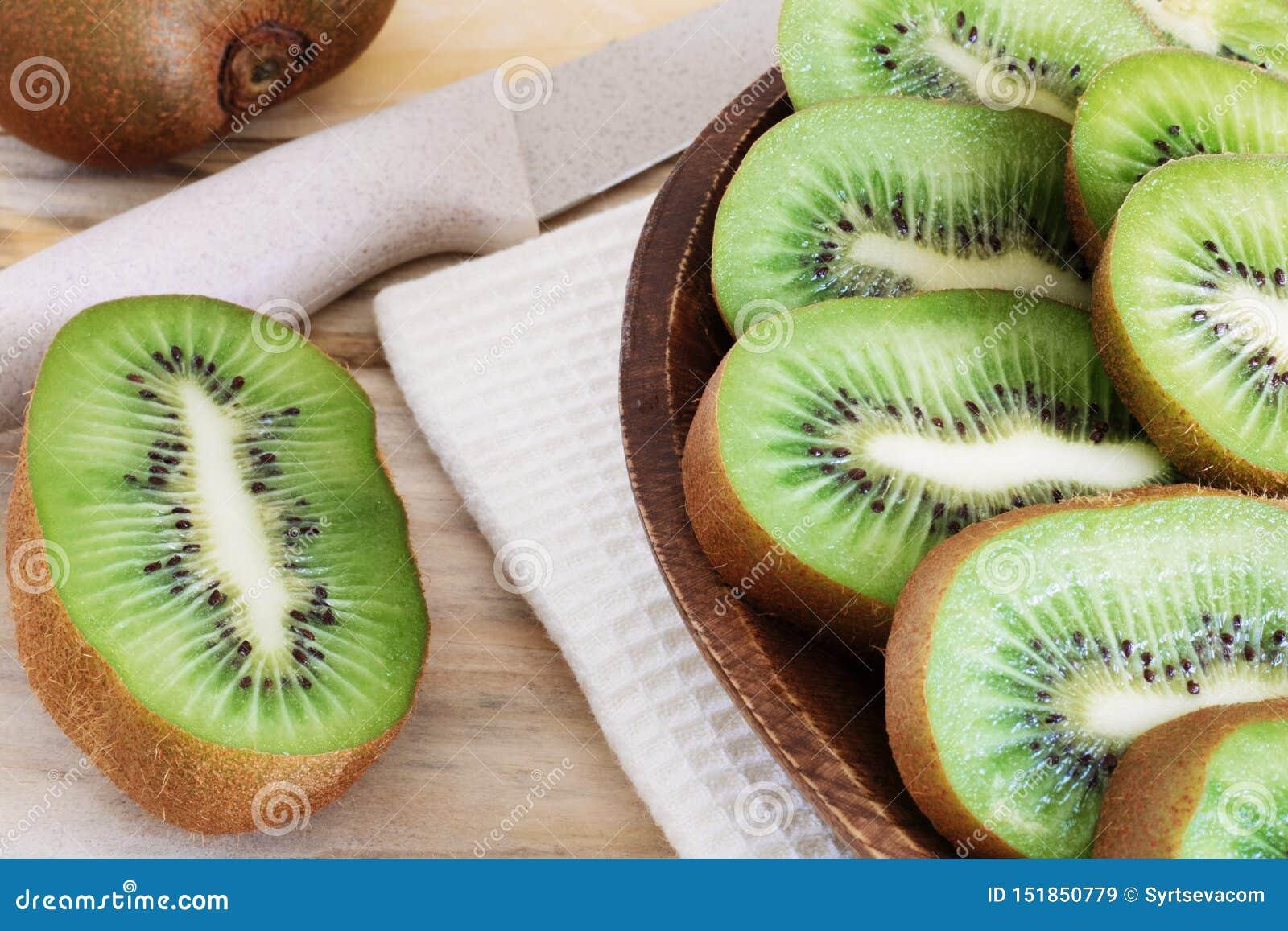 Rebanadas jugosas del kiwi en una placa de madera en el primer de la tabla, madera deliciosa de la fruta, productos dietéticos, i