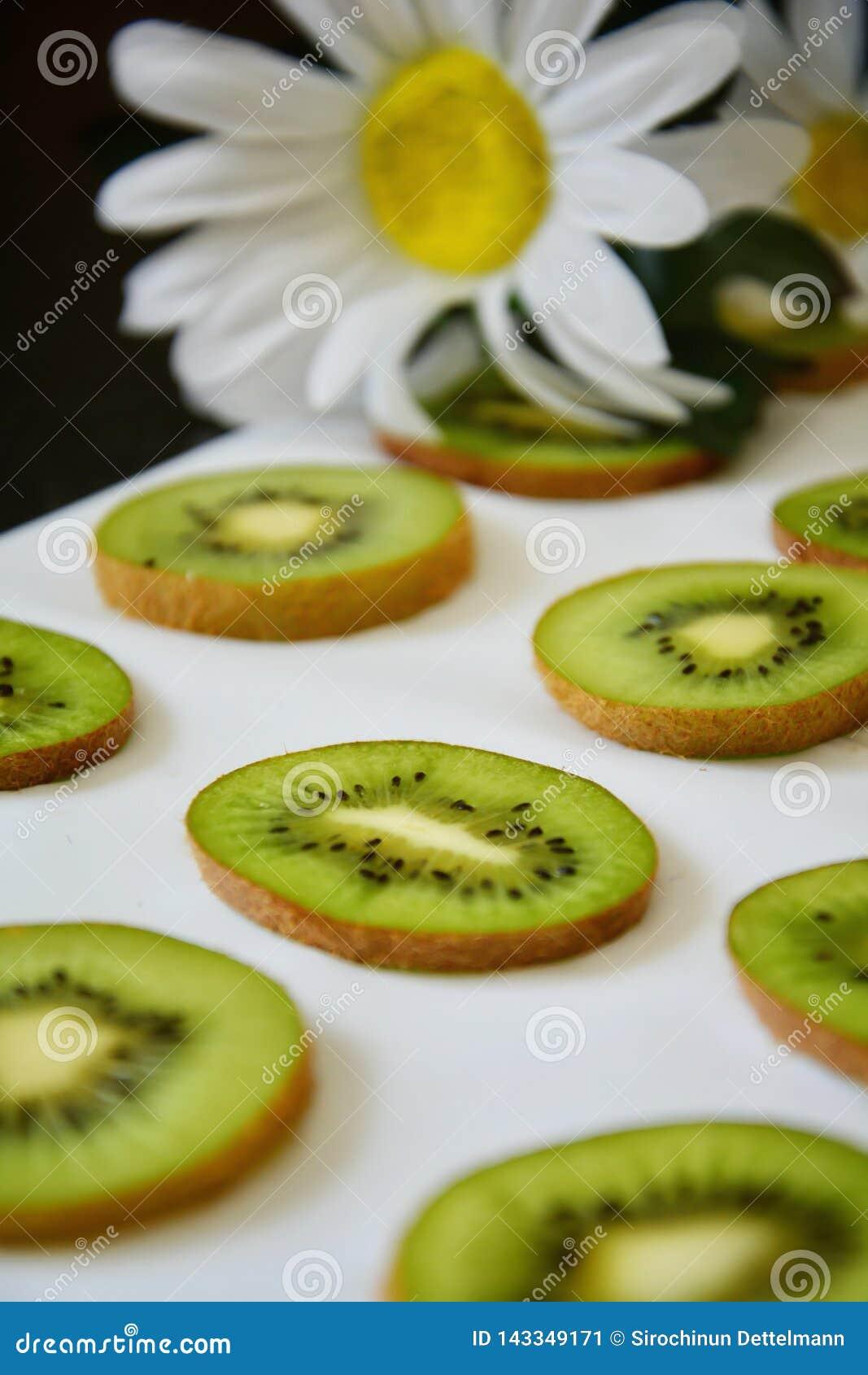 Rebanadas verdes de fruta de kiwi en el fondo blanco