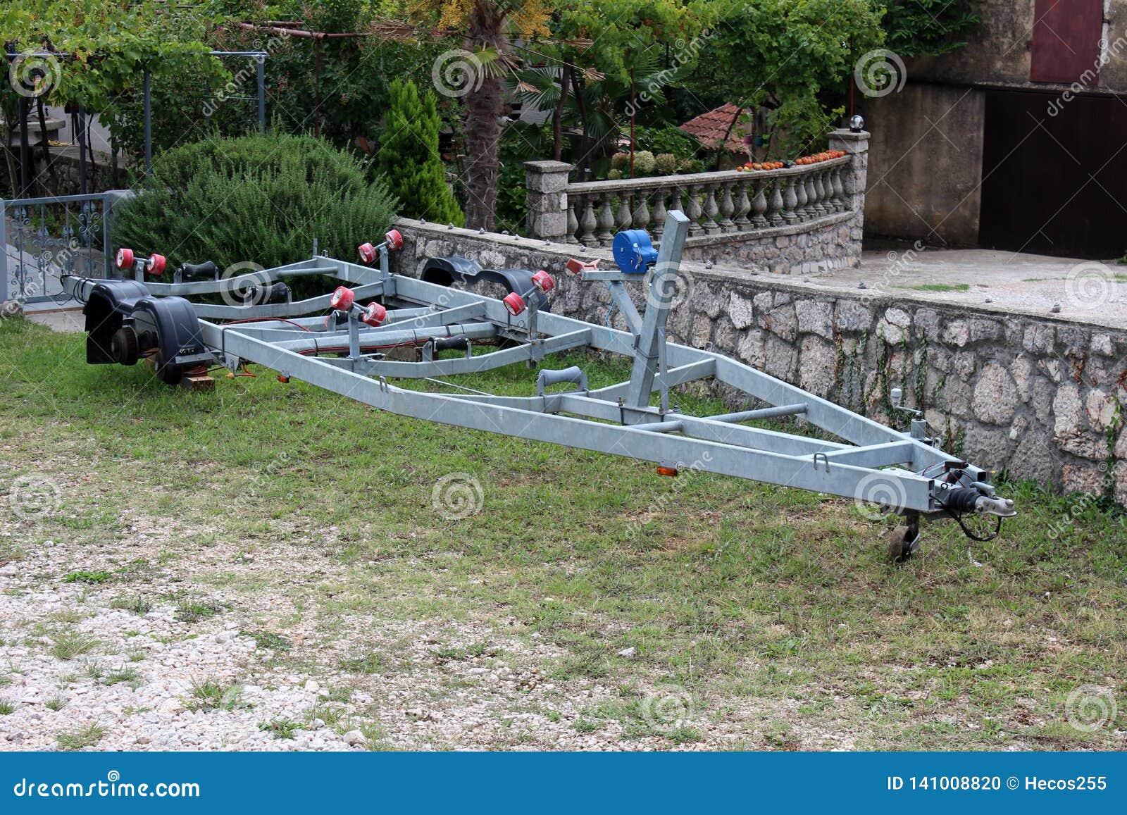 Reboque do barco do metal estacionado no quintal sem pneumáticos que esperam o verão ao lado da parede de pedra tradicional com g