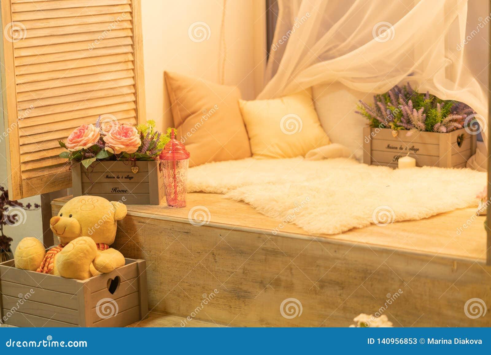 Rebord de fenêtre avec les oreillers, la fourrure blanche, l ours de nounours et les fleurs personne