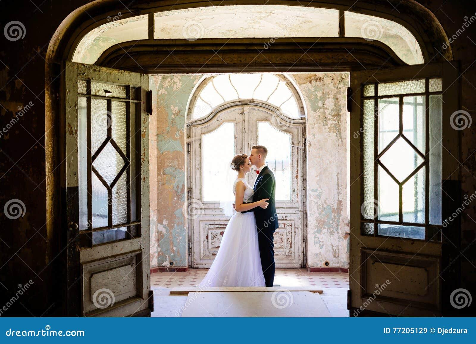Recém-casados que abraçam na porta em uma casa velha