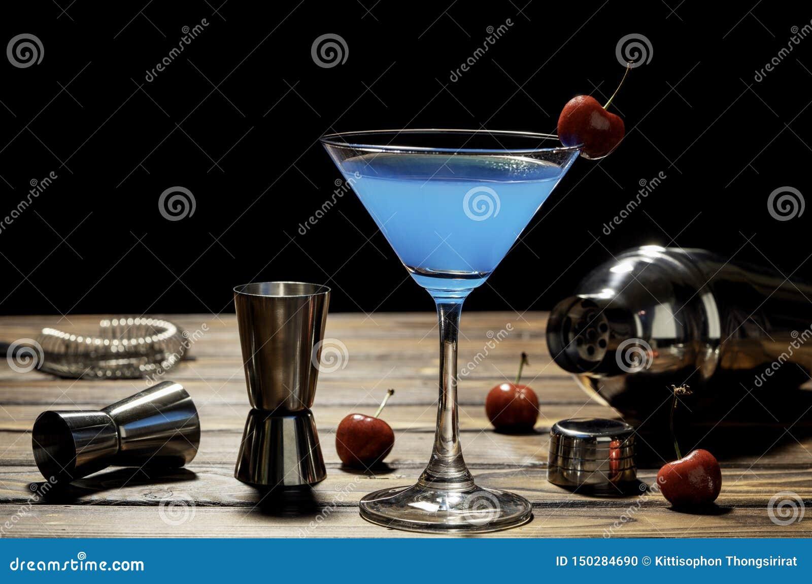 Receita azul de martini do cocktail colorido com os acessórios vermelhos da cereja e do barman na tabela de madeira no fundo pret