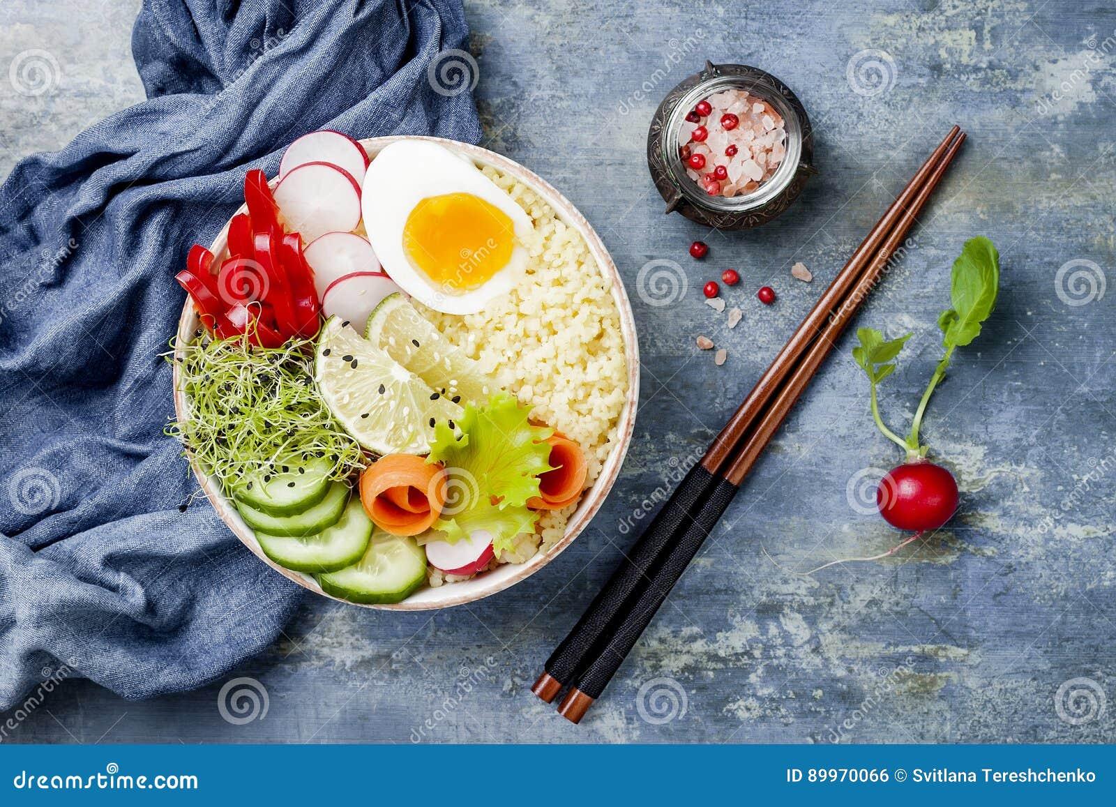 Receita da bacia da Buda da desintoxicação dos vegetarianos com ovo, cenouras, brotos, cuscuz, pepino, rabanetes, sementes Vista