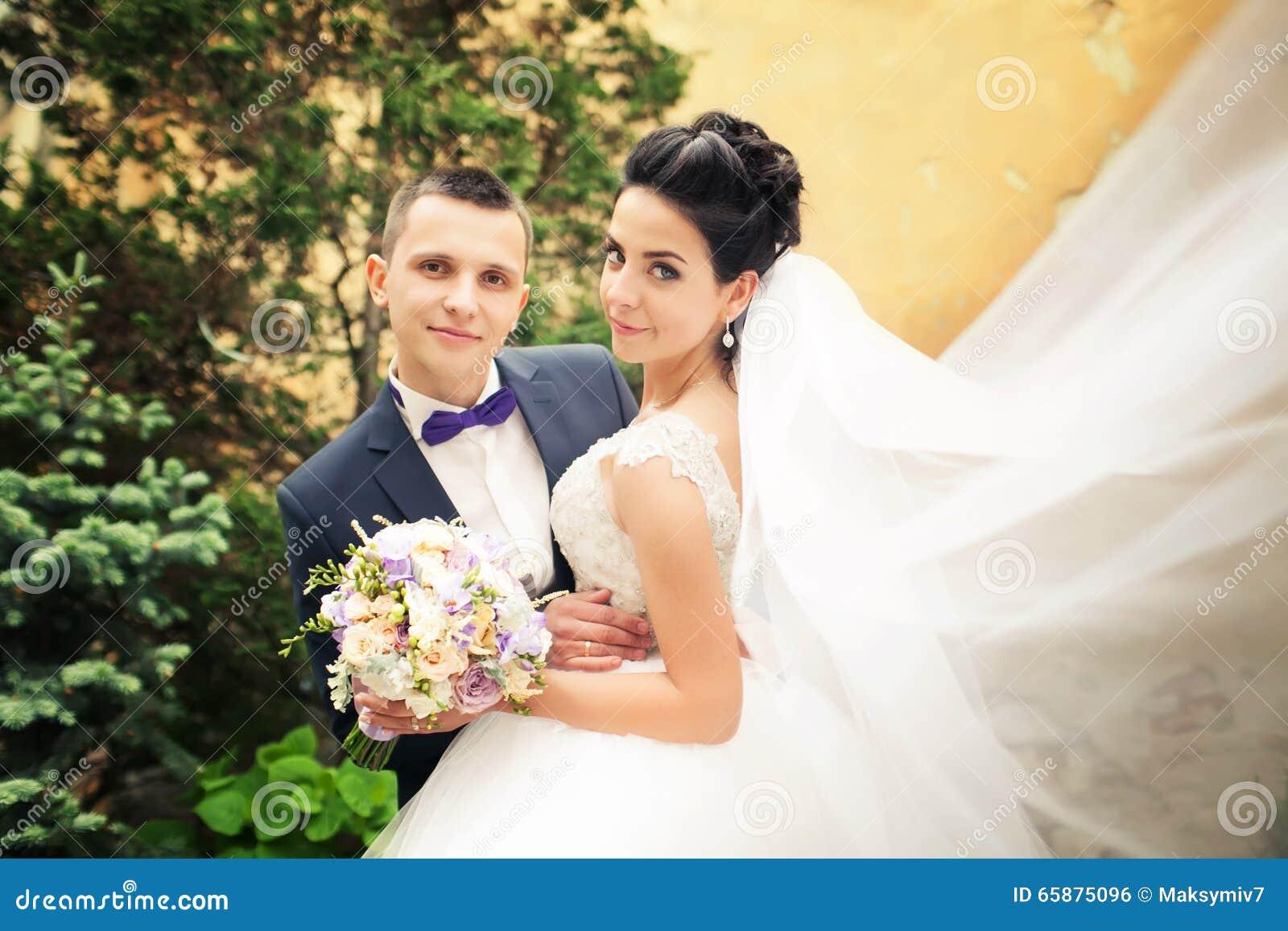 Recentemente baciare della coppia sposata Vento che solleva velo nuziale bianco lungo