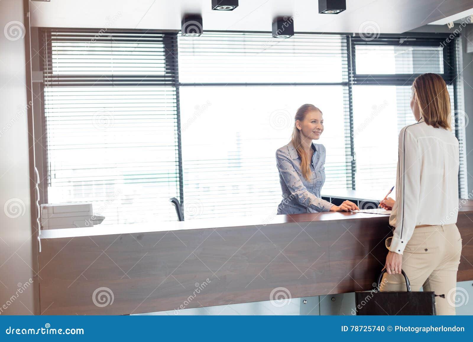 Recepcionista de sexo femenino joven que mira el documento de firma de la empresaria en oficina