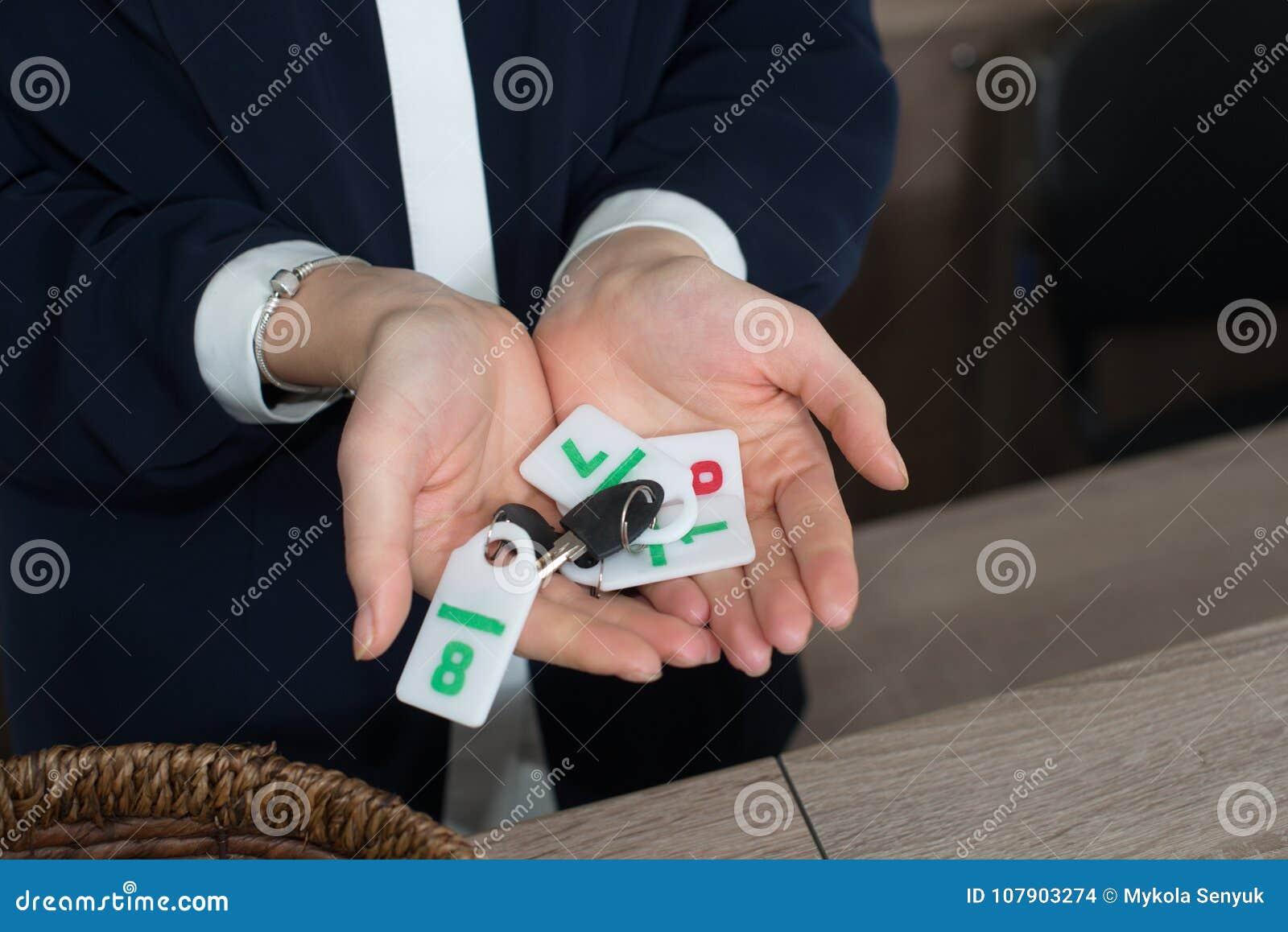 Recepcionista na recepção da pensão que mostra chaves com dígitos ao convidado ou ao cliente