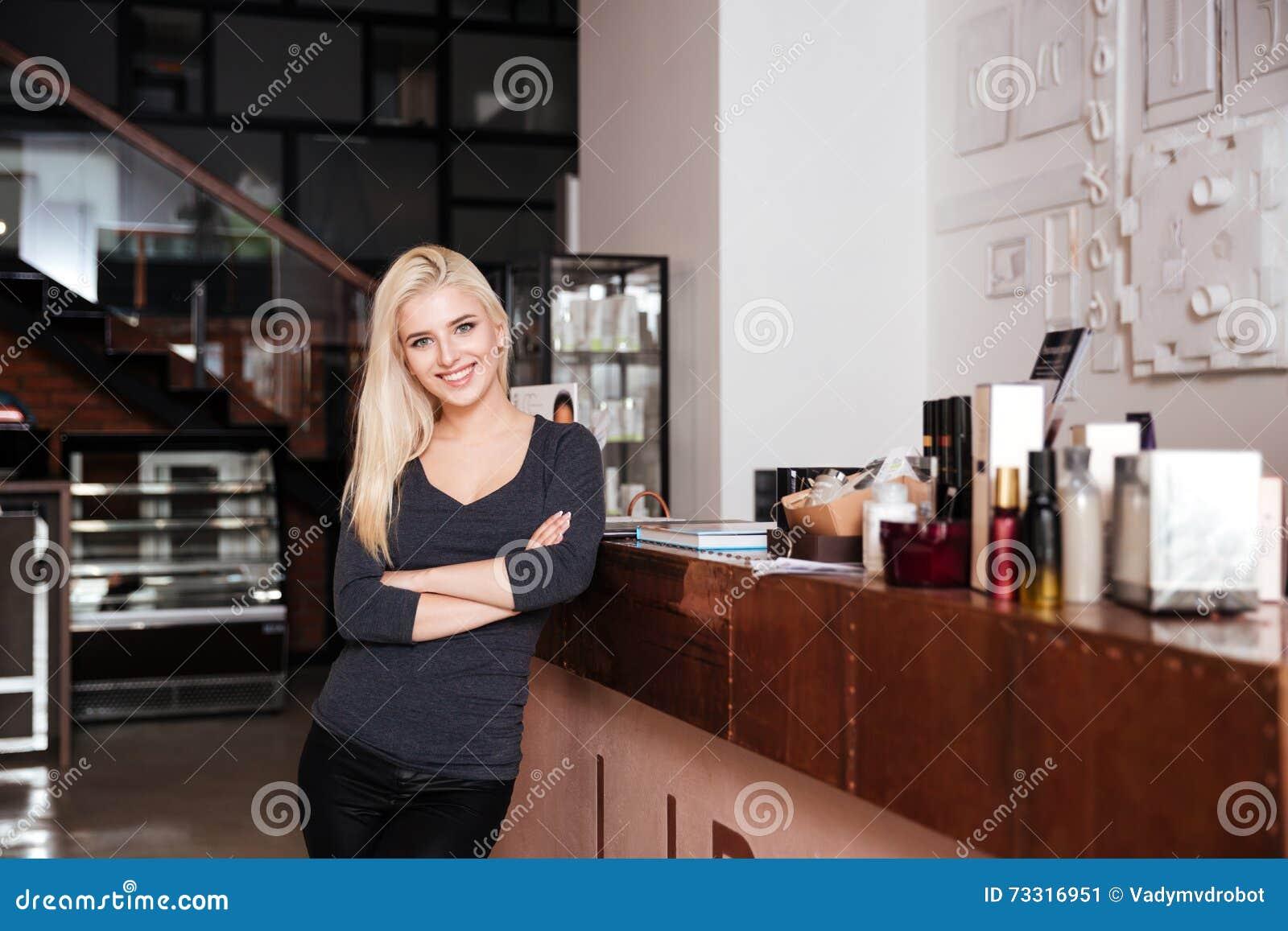 Receptionist femminile del salone di bellezza che sta con le mani attraversate