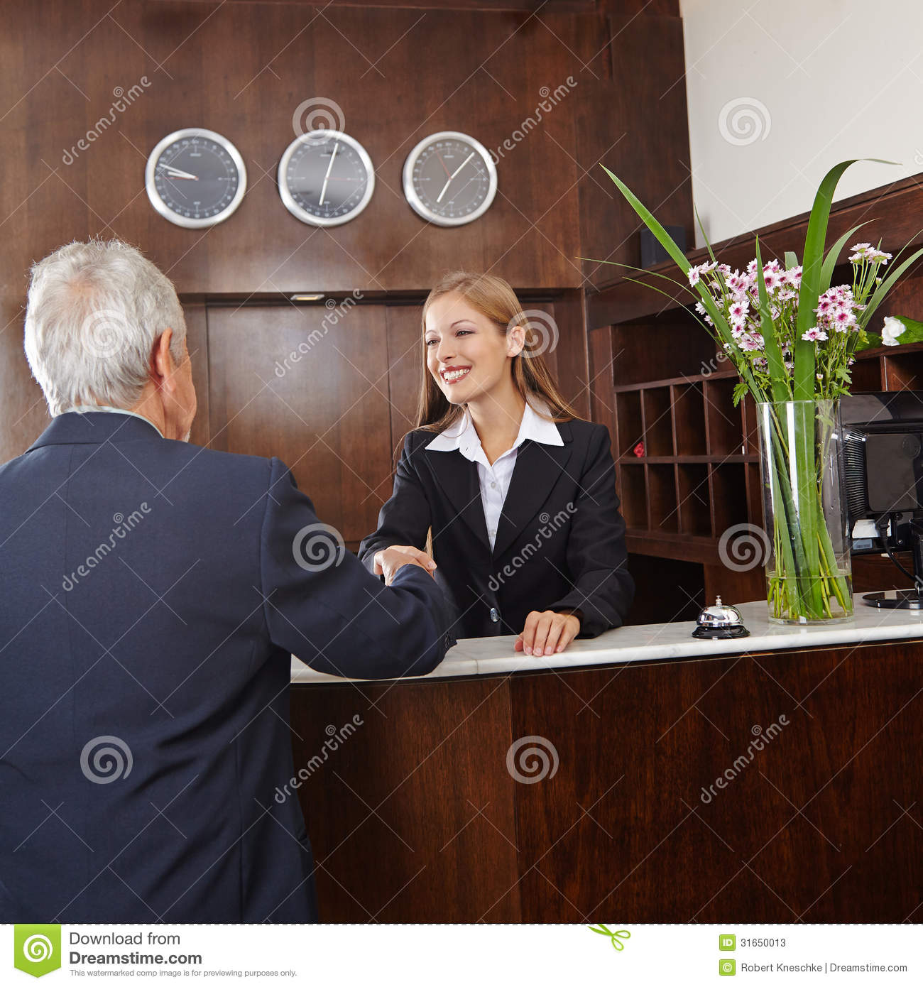 Receptionist Giving Handshake To Senior Guest Stock Image