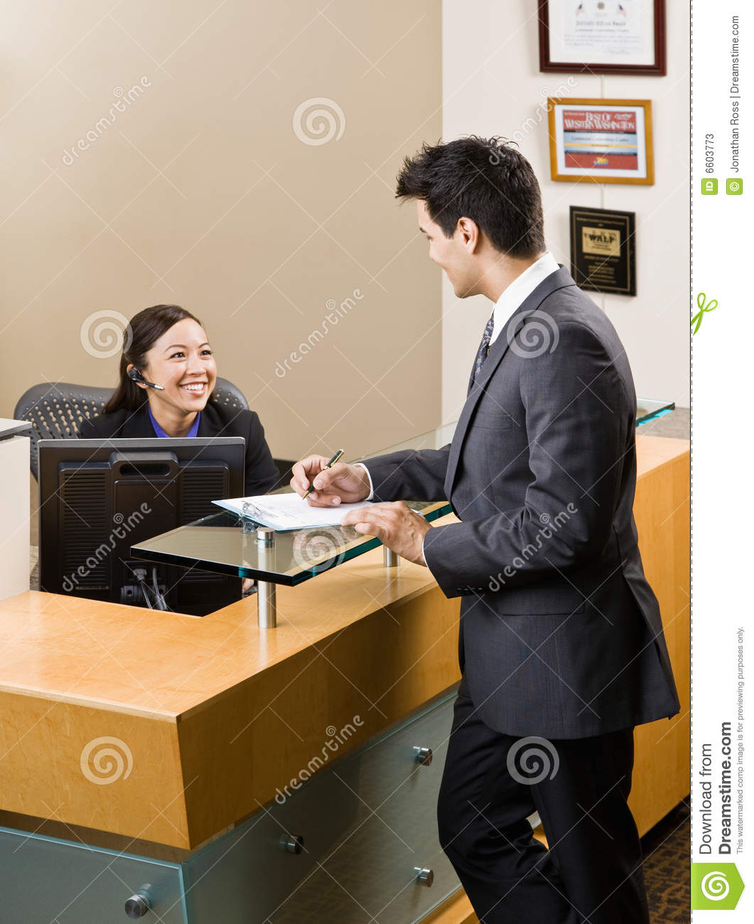 Receptionist greeting man at front desk