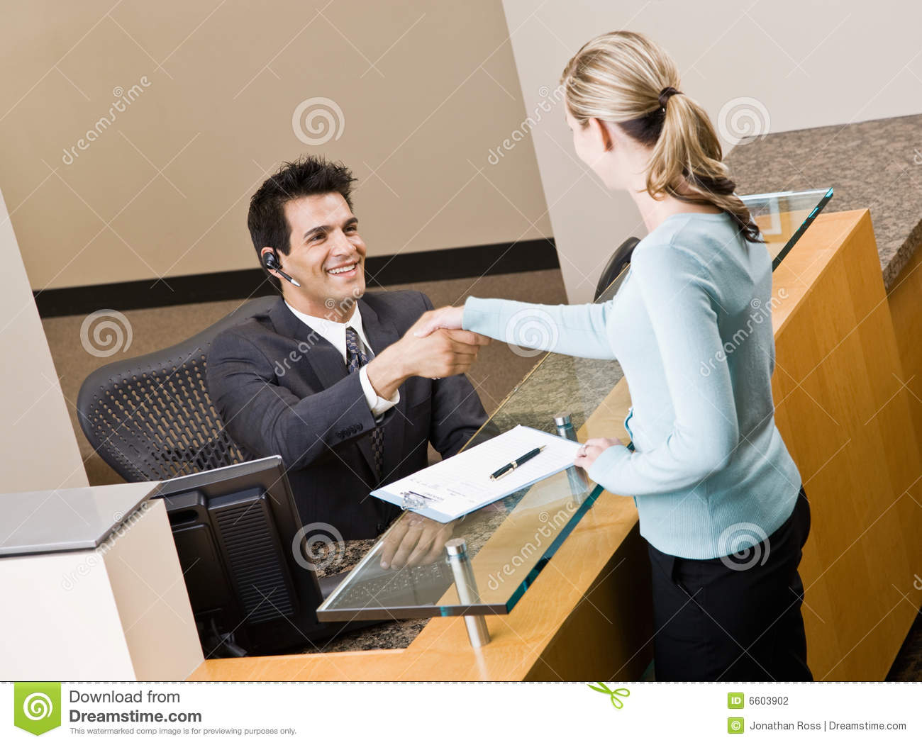 Underground Parking Receptionist Greeting Woman At Front Desk Stock