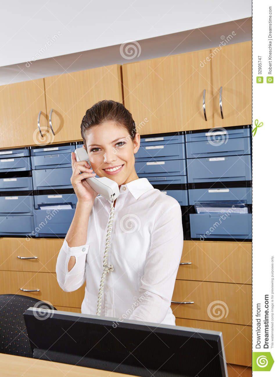 Young receptionist in a hospital taking a phone call Hospital Receptionist