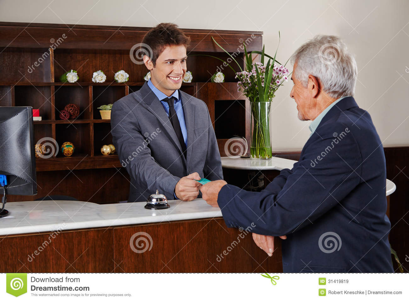 Receptionist In Hotel Giving Key Card To Senior Royalty