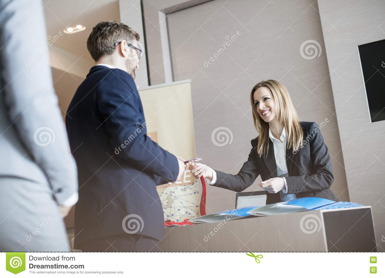 Receptionist som ger identitetskortet till affärsmannen på konventcentret