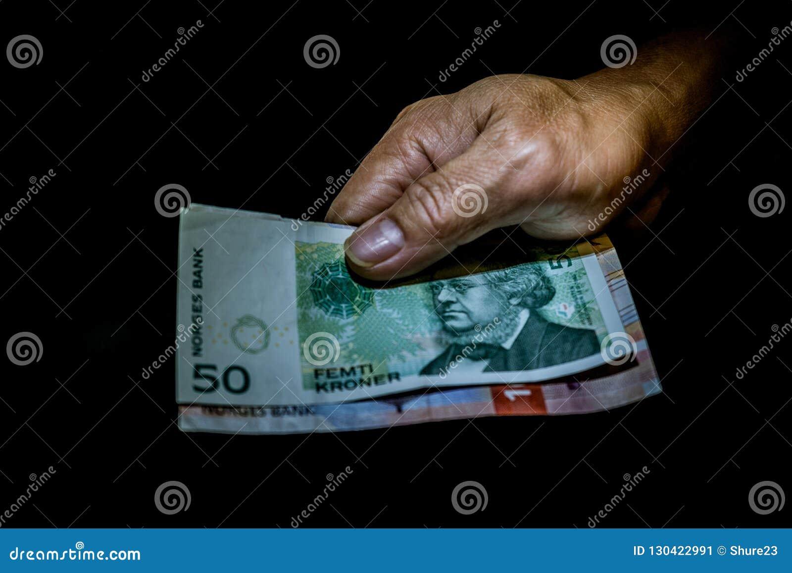Rechnungen der norwegischen Kronen in der Hand einer Person lokalisiert auf Schwarzem