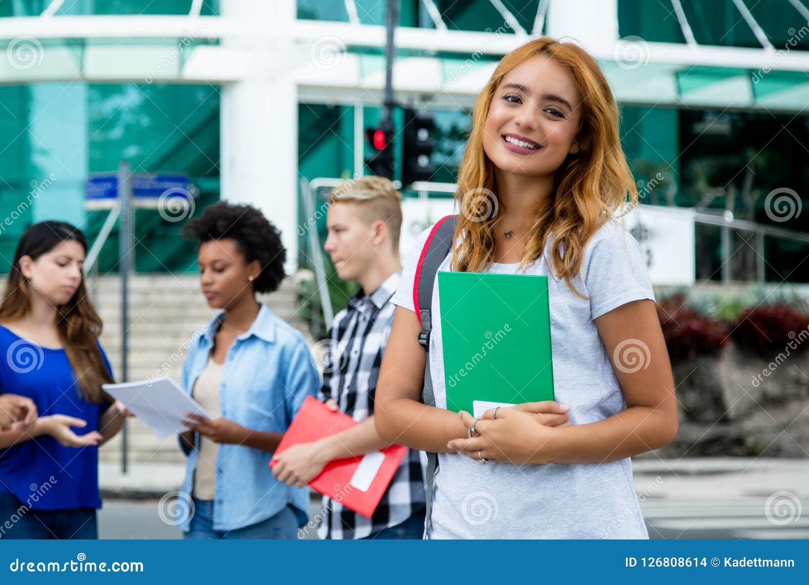 Recht amerikanische Studentin mit Gruppe internationalem peopl