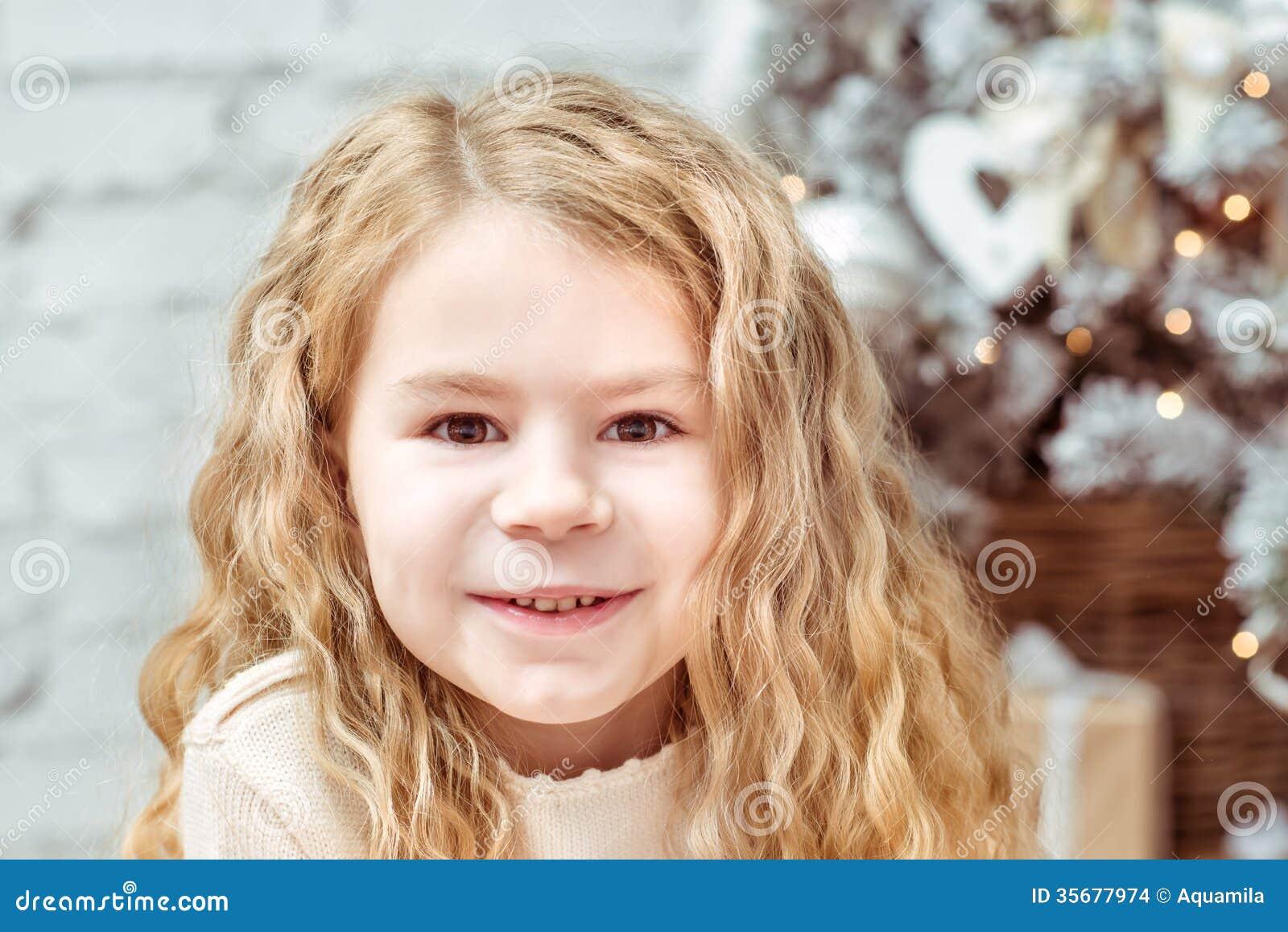 Recht blondes kleines Mädchen, das unter dem Weihnachtsbaum sitzt